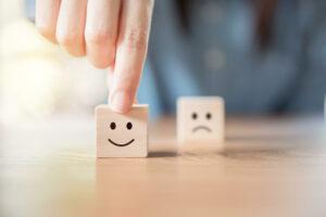 Finger Selecting Smiley Face Over Unhappy Face